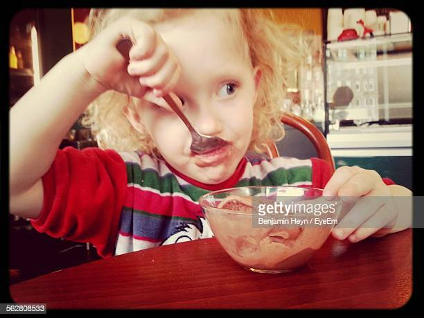 Girl Eating Chocolate Ice Cream From Bowl At Home