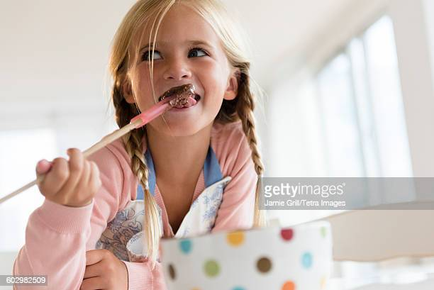 Girl (6-7) eating chocolate