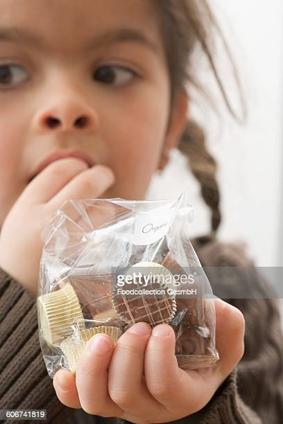 Girl eating chocolates out of a bag
