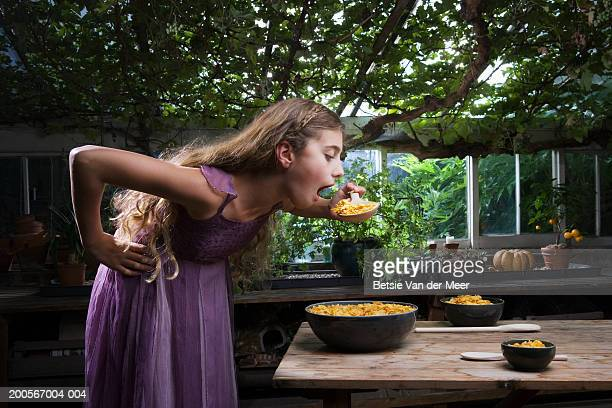 girl (10-11) eating cornflakes from the largest of three bowls on table in greenhouse - goldilocks stock photos and pictures