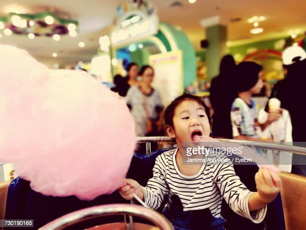 Girl Eating Cotton Candy In Shopping Mall