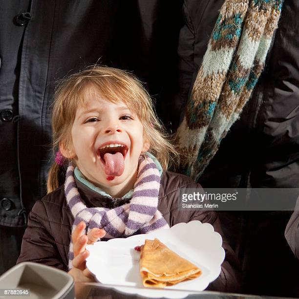 Girl eating crepe with jam