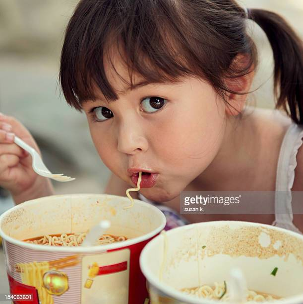 Girl eating cup noodle.
