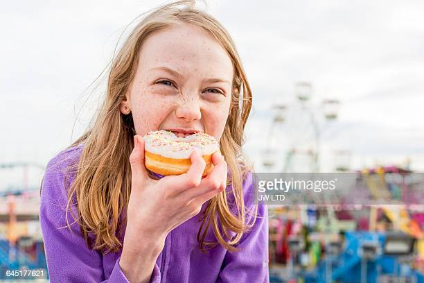 girl (8-9) eating donut, funfair - carnival stock pictures, royalty-free photos & images