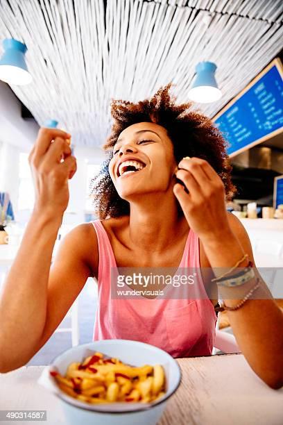 Girl eating french fries in restaurant