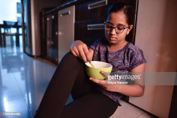 girl eating from bowl while sitting on kitchen floor - eating disorder stock pictures, royalty-free photos & images