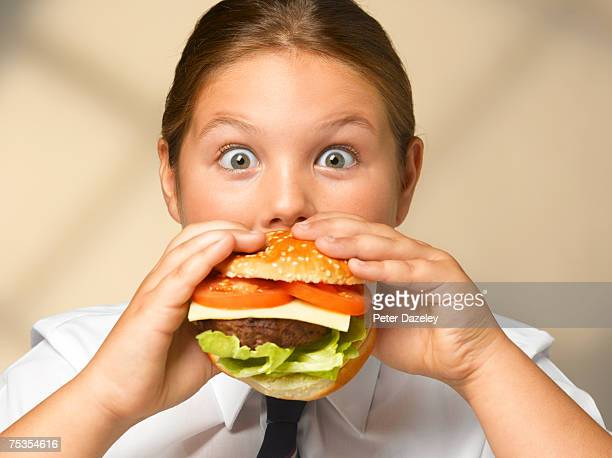Girl (8-10) eating hamburger, portrait, close-up