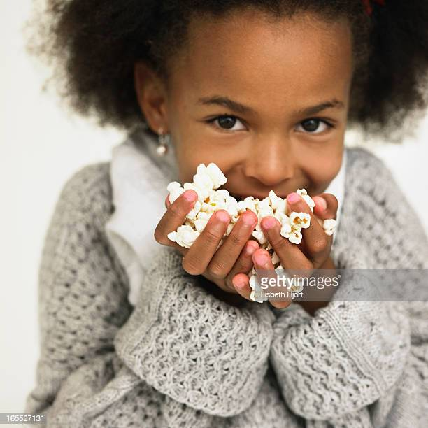 girl eating handful of popcorn - handful stock pictures, royalty-free photos & images