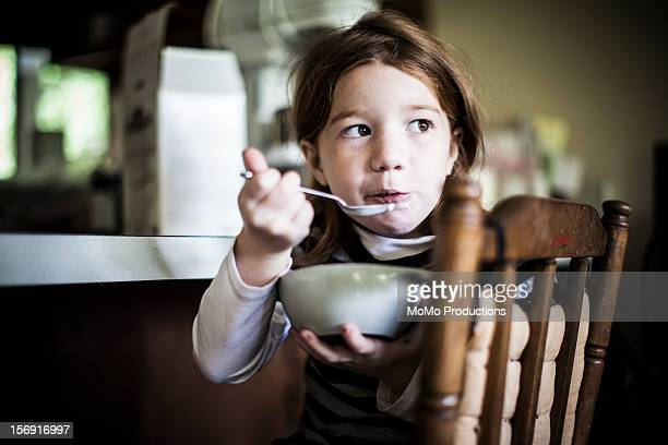 Girl (6yrs) eating homemade yogurt from bowl