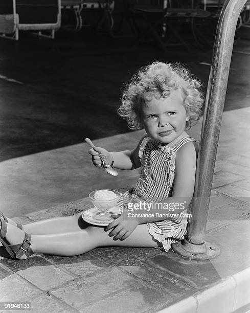 girl eating ice cream sitting next to pool - number of people stock pictures, royalty-free photos & images