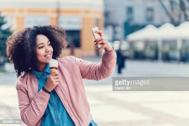 Fille, manger des glaces et prise selfie