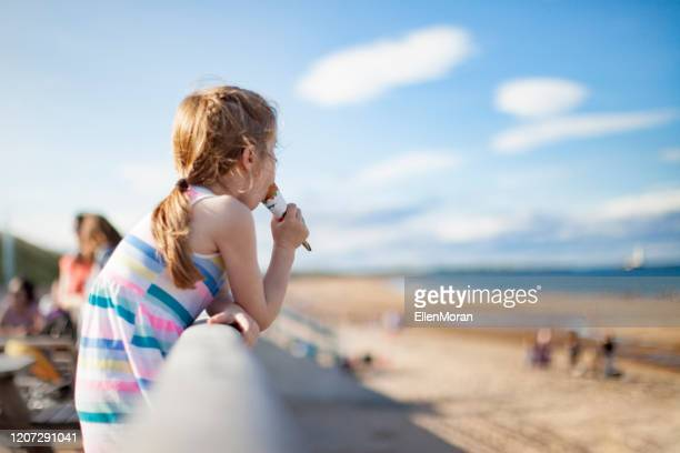 girl eating ice-cream at the beach - beach stock pictures, royalty-free photos & images