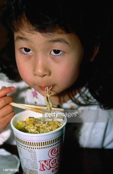 Girl eating instant noodles.