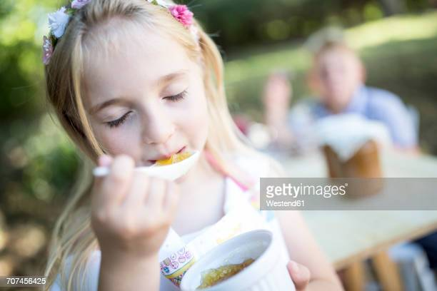 Girl eating jelly outdoors
