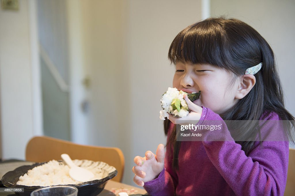 Girl eating large rice parcel at dining table : Stock Photo
