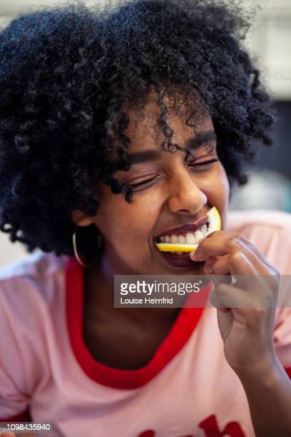 girl eating lemon - sour taste stock pictures, royalty-free photos & images