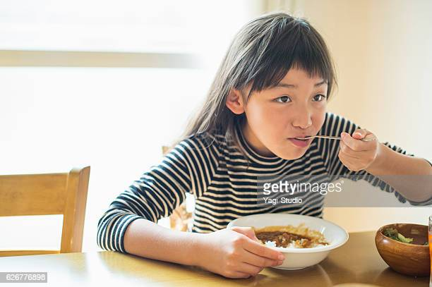 girl eating lunch in dining room - curry meal stock pictures, royalty-free photos & images