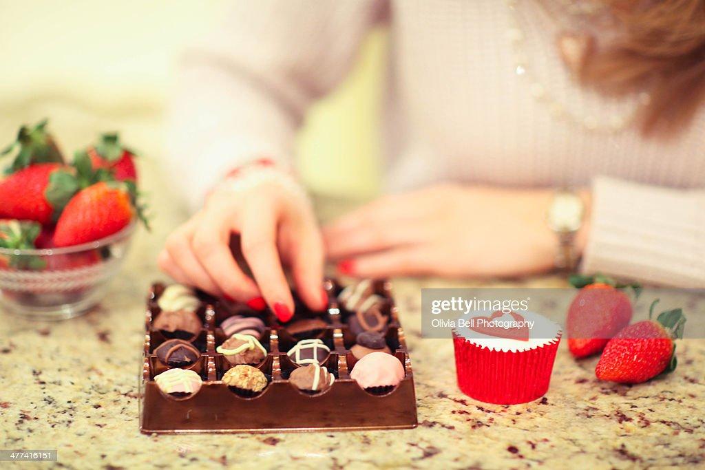 Girl Eating Luxury Chocolates and Strawberries : Stock Photo
