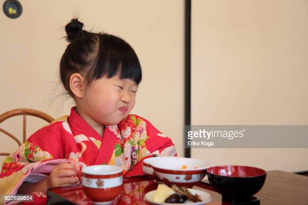 girl eating new year's japanese traditional food called osechi - osechi ryori stock pictures, royalty-free photos & images