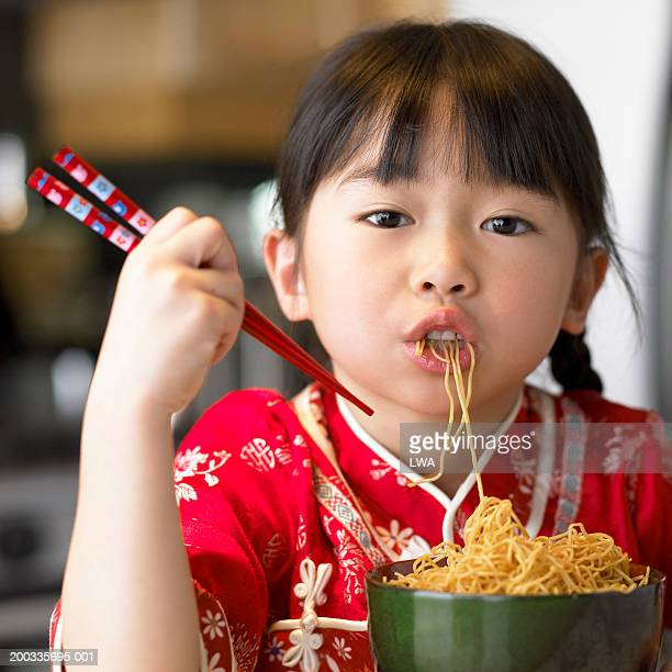 Girl (6-8) eating noodles with chopsticks, portrait, close-up
