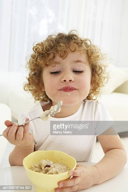 Girl (4-5 years) eating oatmeal from bowl