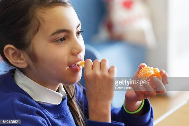 Girl eating orange in school