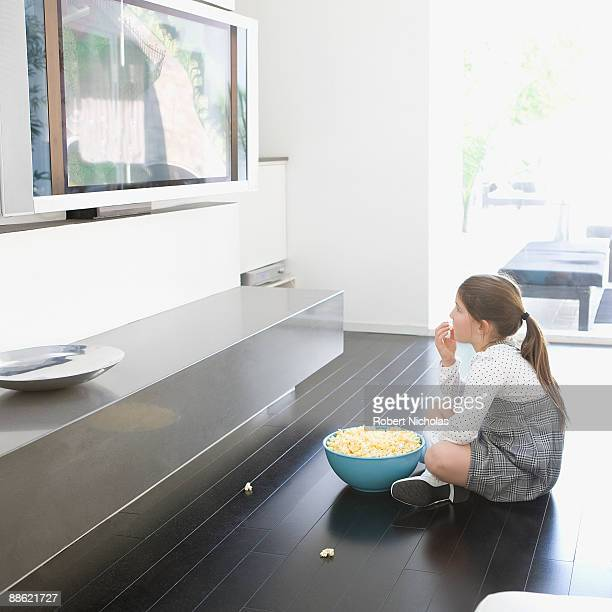 Girl eating popcorn and watching television