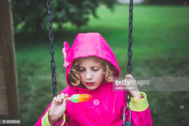 Girl Eating Popsicle in Rain Coat