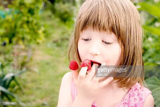 Girl eating raspberries off fingers, close up