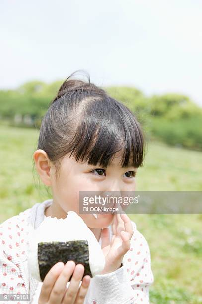 girl eating rice ball - rice ball stock pictures, royalty-free photos & images