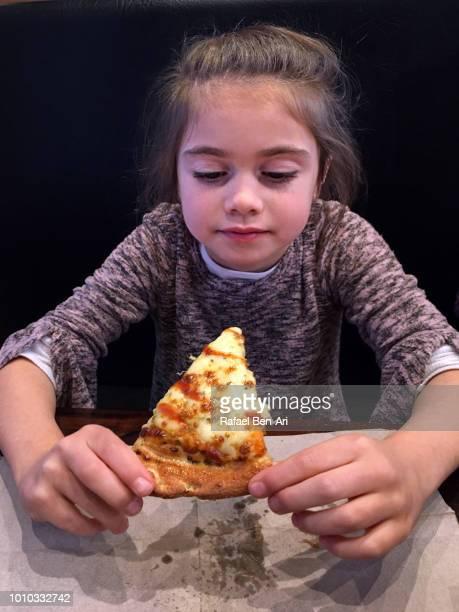 girl eating slice of pizza - rafael ben ari stock-fotos und bilder