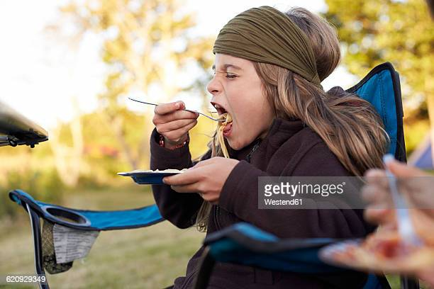 Girl eating spaghetti on a camping ground