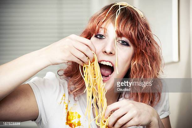 Girl eating spaghetti with hands