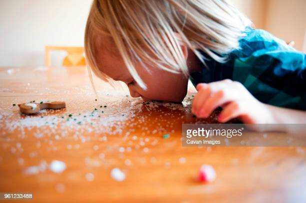 girl eating sprinkles from wooden table at home - dirty little girls photos stock pictures, royalty-free photos & images