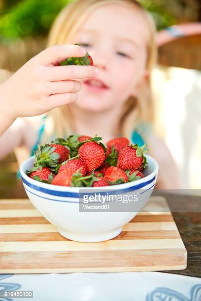 Girl eating stawberries form bowl