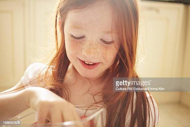Girl eating strawberries in kitchen