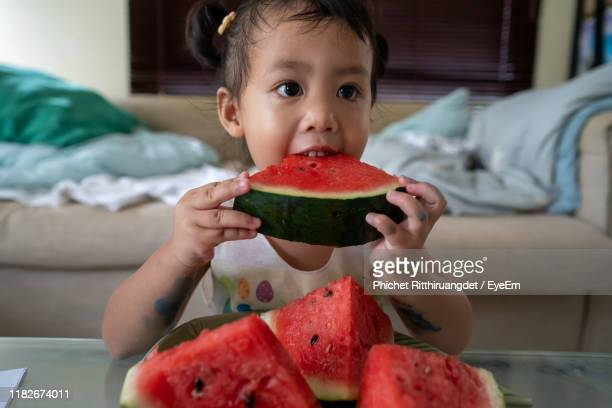 girl eating watermelon at home - phichet ritthiruangdet stock photos and pictures