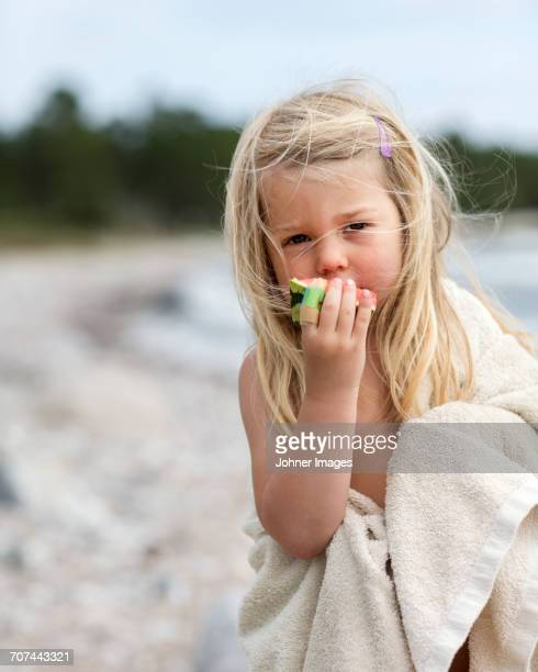 Girl eating watermelon on beach