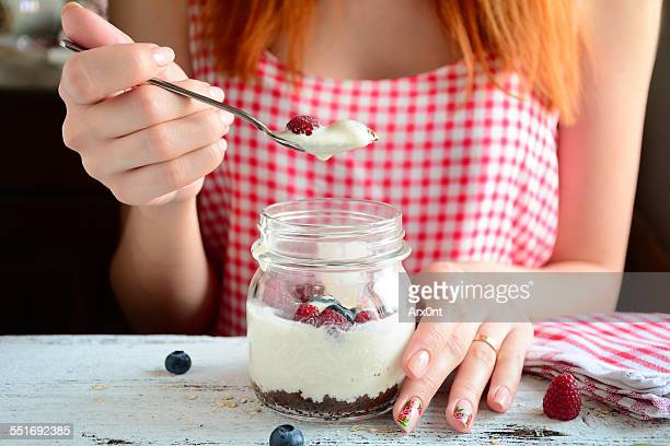 Girl eating yogurt dessert in jar. Breakfast