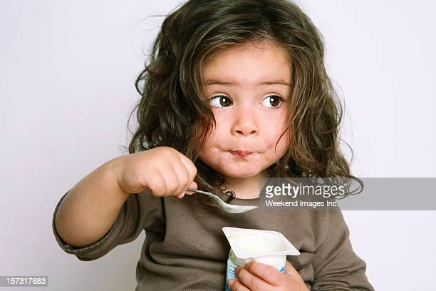 girl eating yogurt - peuter stockfoto's en -beelden
