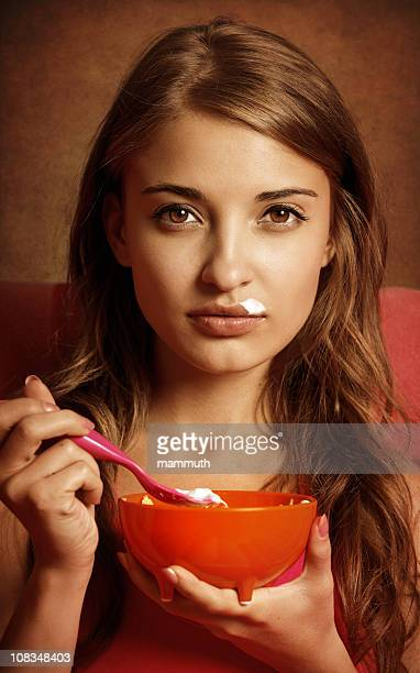 Fille mangeant des yaourts avec corn flakes