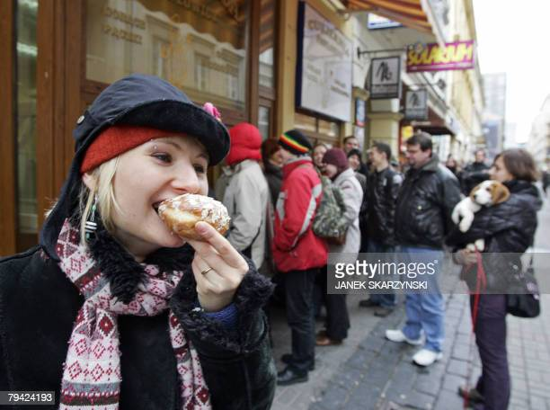 A girl eats a doughnut as other customers queue in front of a pastry shop in Warsaw on Fat Thursday as Poles snap up the lipsmacking plump...
