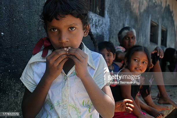 Girl eats a 'Kottamba'seed as her colleagues living in a shanty neighborhood look on at Negombo,approximately 38 km from capital city, Colombo,...
