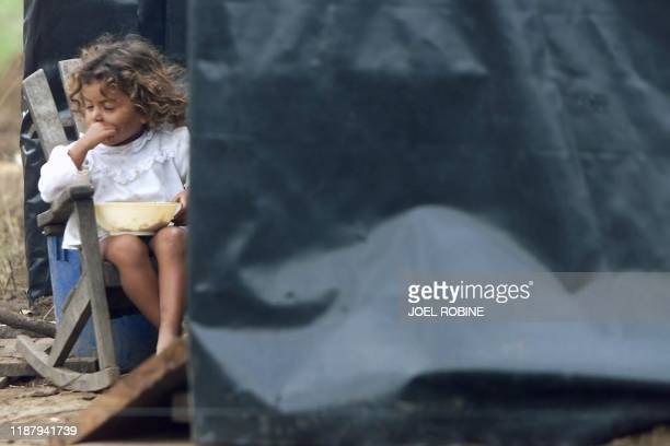 A girl eats a meal 09 November in the New Life Quarter a camp of plastic sheeting and shacks installed at Ciudad Sandino 15 kilometers from Lake...