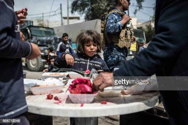 A girl eats food distributed by Shia volunteers during fighting against Islamic State in west Mosul on April 12 2017 in Mosul Iraq Despite being...