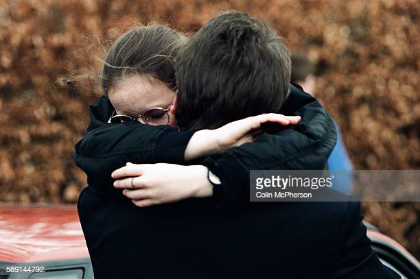 A girl embracing an adult outside Dunblane primary school Scotland shortly after the shooting incident on the premises The Dunblane school massacre...