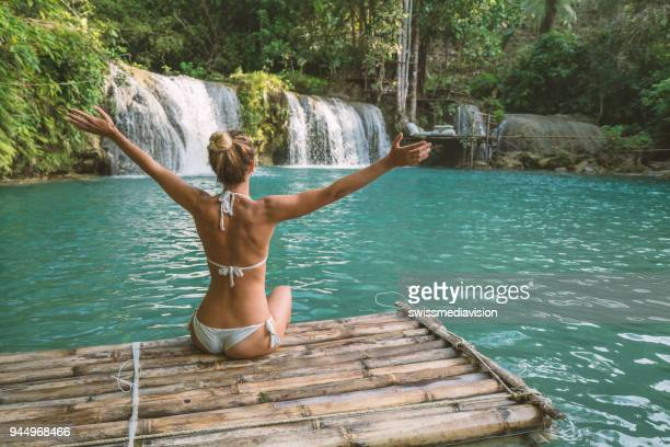 Girl embracing beautiful waterfall in the Philippines