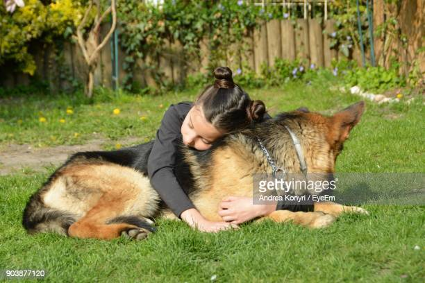 Girl Embracing Dog While Lying On Grassy Field
