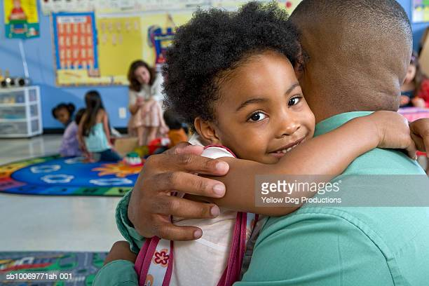 Girl (4-5) embracing father in classroom