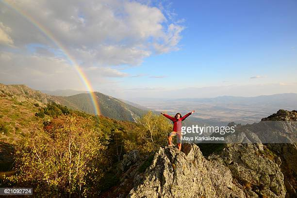 Girl embracing happiness next to a rainbow